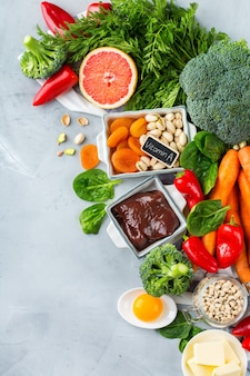 Ausgewogene ernährung, gesundes, sauberes esskonzept. auswahl an vitamin-a-reichen nahrungsquellen auf einem küchentisch. raumhintergrund kopieren