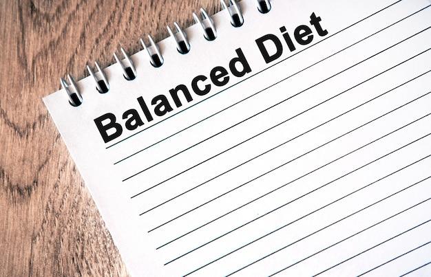 Ausgewogene ernährung - schwarzer text auf einem weißen notizbuch mit linien auf einem holztisch