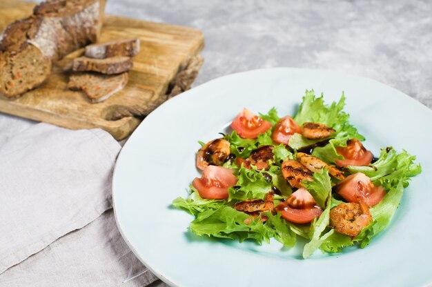 Ausgewogene gesunde ernährung, grüner salat mit gegrillten garnelen und kirschtomaten unter balsamico.