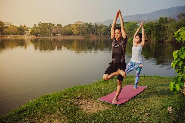 Ausgewogene yoga-partner neben dem see