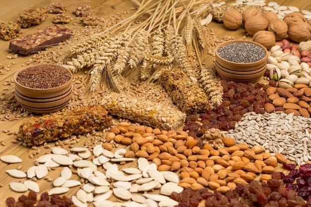 Ausgewogener protein-müsliriegel. nüsse, samen, getreide, ährchen von weizen. gesunde ernährung vegetarisches essen. draufsicht. holzoberfläche. nahansicht