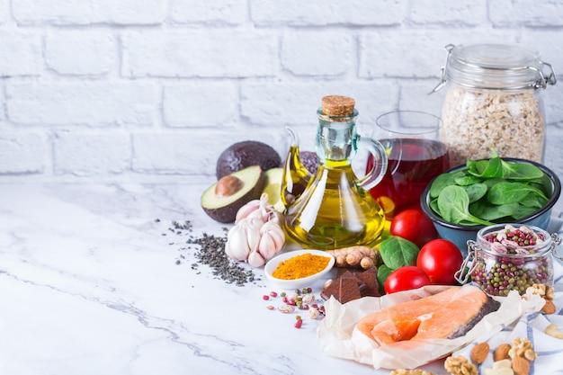 Ausgewogenes ernährungskonzept. auswahl an gesunden lebensmitteln cholesterinarm, spinat avocado rotwein grüner tee lachs tomate leinsamen chiasamen kurkuma knoblauch nüsse olivenöl