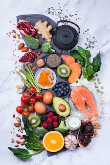 Ausgewogenes ernährungskonzept für eine saubere ernährung. auswahl an gesunden lebensmitteln, superfood-zutaten zum kochen auf einem küchentisch. draufsicht flach legen hintergrund