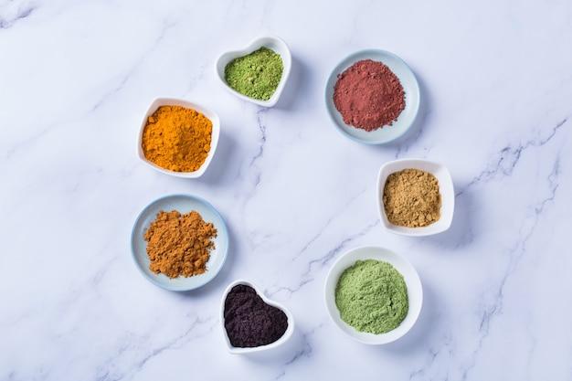 Ausgewogenes ernährungskonzept für eine saubere ernährung mit antioxidativer detox-diät. auswahl an superfood-pulver - acai, kurkuma, weizen, ingwer, zimt, matcha. flach legen, marmorhintergrund kopieren