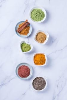 Ausgewogenes ernährungskonzept für eine saubere ernährung mit antioxidativer detox-diät. auswahl an superfood-pulver - acai, kurkuma, weizen, ingwer, zimt, matcha. flacher marmorhintergrund