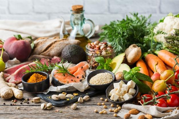 Ausgewogenes ernährungskonzept für eine saubere, flexitäre mediterrane ernährung. auswahl an gesunden lebensmittelzutaten zum kochen auf einem hölzernen küchentisch.