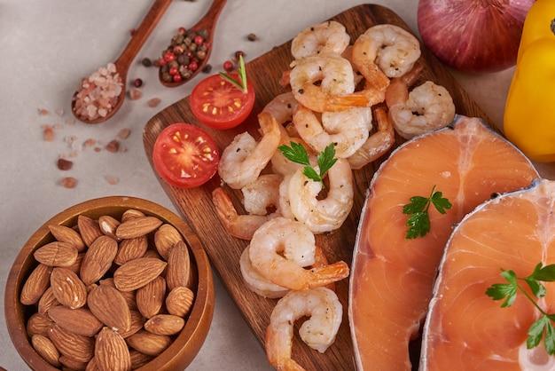Ausgewogenes ernährungskonzept für sauberes essen flexitäre mittelmeerdiät draufsicht flach. ernährung, sauberes essen lebensmittelkonzept. diätplan mit vitaminen und mineralstoffen. lachs und garnelen, gemüse mischen