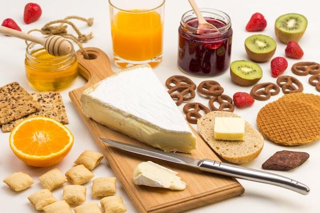 Ausgewogenes proteinfrühstück. brie käse auf schneidebrett. kekse, obst und beeren, orangensaft im glas, marmelade und honig im glas. flach liegen. weiße oberfläche.