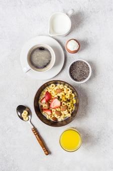Ausgewogenes traditionelles frühstück und zutaten. vollkornringe cheerios, kaffee, orangensaft und ei.