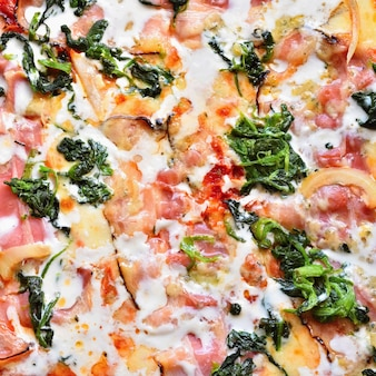 Ausgezeichnete frische pizza mit käse, speck, sahne und spinat. leckeres schnelles italienisches essen.