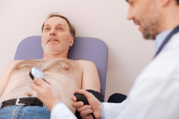 Ausgezeichneter kompetenter junger fachmann, der ein spezielles blutdruckmessgerät verwendet, während er eine allgemeine untersuchung der gesundheit des mannes durchführt