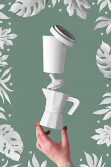 Ausgleich der null-abfall-kaffeepyramide in den weiblichen händen auf salbei grünem hintergrund. keramik-espressomaschine und umweltfreundliche wiederverwendbare bambus-kaffeetasse. kaffeebohnen und exotische papierblätter herum.