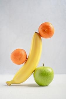 Ausgleich oder schweben reife orange mandarine, gelbe banane und grüner apfel auf weißem holztisch