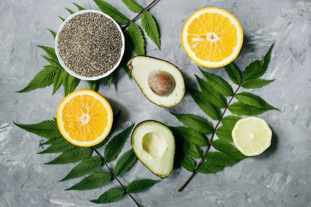 Auslassung einer gesunden ernährung. grüne blätter und früchte (avocado, orange, zitrone), auf grauem hintergrund. sommerkonzept. flache lage, draufsicht, kopierraum.