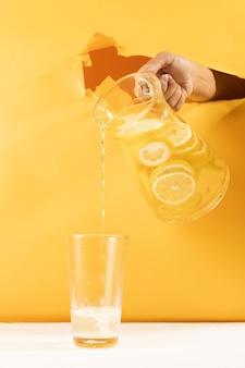 Auslaufende limonade der vorderansicht hand