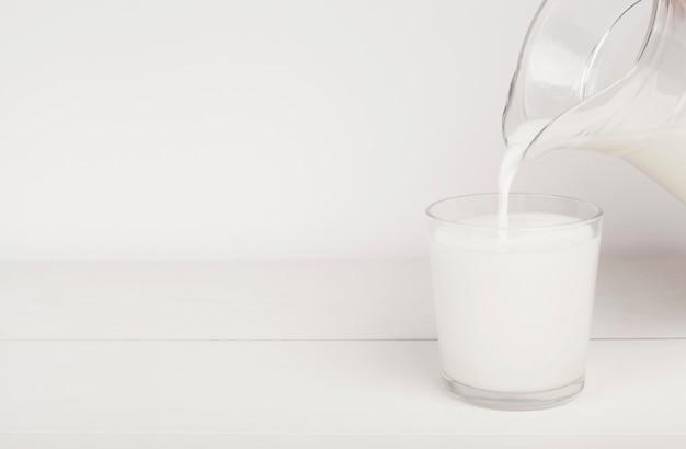 Auslaufende milch in einem glas mit kopienraum