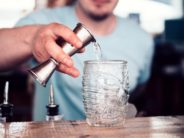 Auslaufender alkohol des unerkennbaren barkeepers im glas
