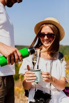 Auslaufender kaffee des mannes in einer schale von einer thermosflasche