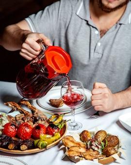 Auslaufender kirschkompott des mannes gedient mit kebabplatten