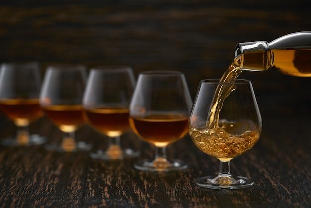Auslaufender kognak aus der flasche in das glas gegen holztisch.