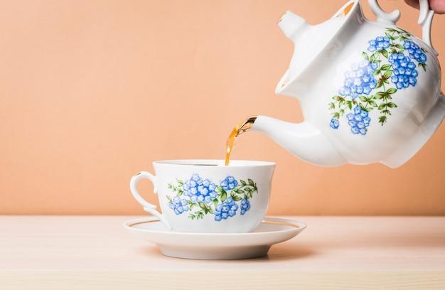 Auslaufender tee des alten porzellankessels vom krug zur tasse tee