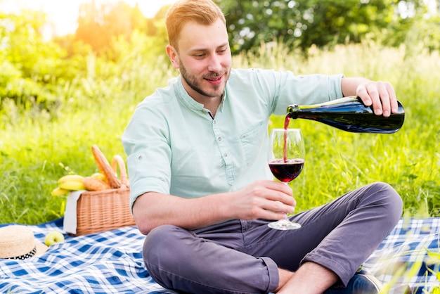Auslaufender wein des mannes, der auf picknickdecke sitzt