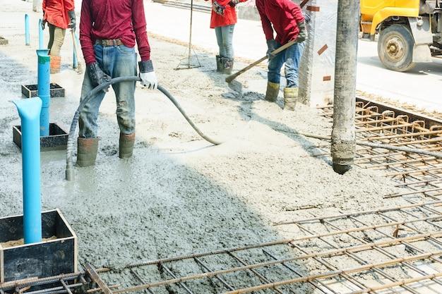 Auslaufender zement oder beton des errichtenden bauarbeiters mit pumpenrohr