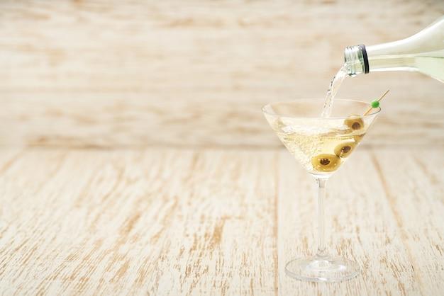 Auslaufendes alkoholisches getränk von der flasche in das glas gegen holztisch.
