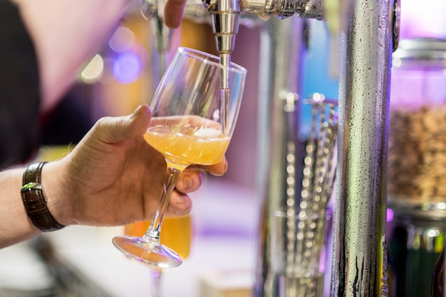 Auslaufendes lagerbier des barmixers in einem glas.