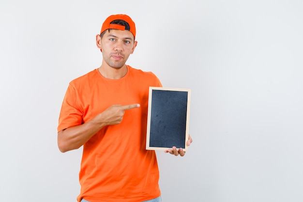Auslieferungsmann, der auf tafel zeigt und im orange t-shirt und in der kappe lächelt