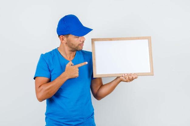 Auslieferungsmann, der finger auf weiße tafel im blauen t-shirt zeigt