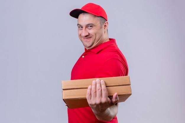 Auslieferungsmann, der rote uniform und kappe hält, die freundlich lächelnde pizzaschachteln mit glücklichem gesicht hält, das über isoliertem weißem raum steht