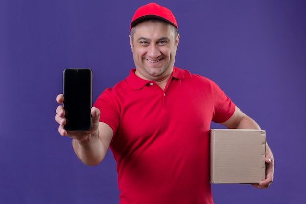 Auslieferungsmann, der rote uniform und kappe hält, die karton hält, zeigt handy, das fröhlich mit glücklichem gesicht steht, das über lila raum steht