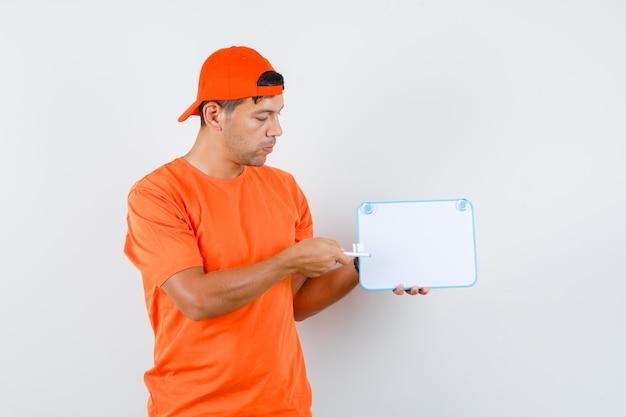 Auslieferungsmann, der stift auf weiße tafel im orange t-shirt und in der vorderansicht der kappe zeigt.