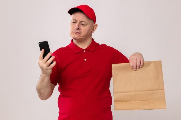 Auslieferungsmann in der roten uniform und in der kappe, die papierpaket hält, das bildschirm seines handys mit ernstem gesicht betrachtet, das über weißem hintergrund steht