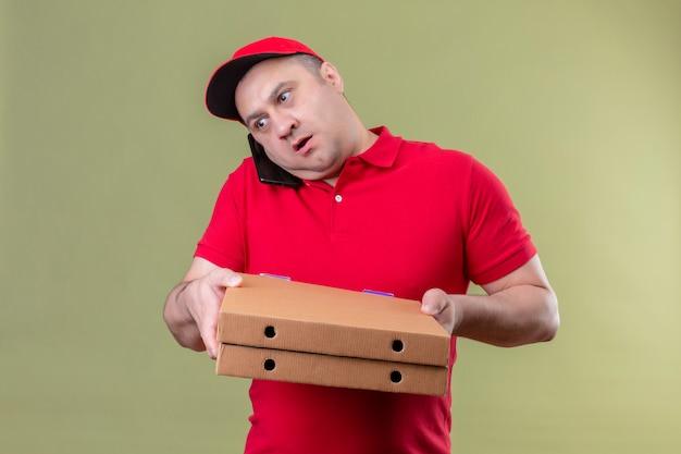 Auslieferungsmann in der roten uniform und in der kappe, die pizzaschachteln halten, während sie auf handy sprechen, das verwirrt steht, das auf lokalisiertem grün steht