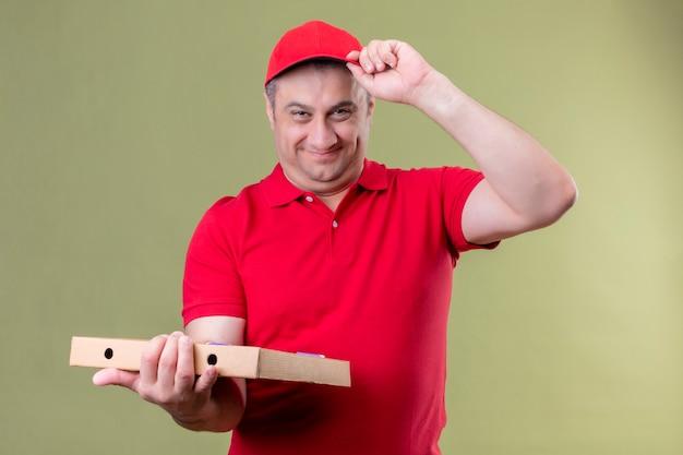 Auslieferungsmann in der roten uniform und in der kappe, die pizzaschachteln positiv und glücklich hält, die seine kappe lächelnd freundlich stehend über isoliertem grünraum berührt