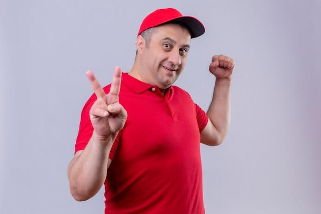 Auslieferungsmann in der roten uniform und in der kappe, die positiv und glücklich lächelnd fröhlich das siegeszeichen mit zwei fingern über isoliertem weißem raum zeigend aussehen