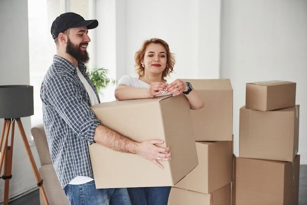 Auspacken der artikel. glückliches paar zusammen in ihrem neuen haus. konzeption des umzugs