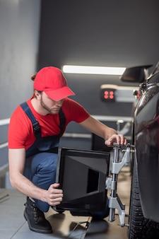 Ausrichtungsständer. konzentrierter ernsthafter junger automechaniker in der arbeitskleidung, die radausrichtungsständer auf autorad in garage installiert