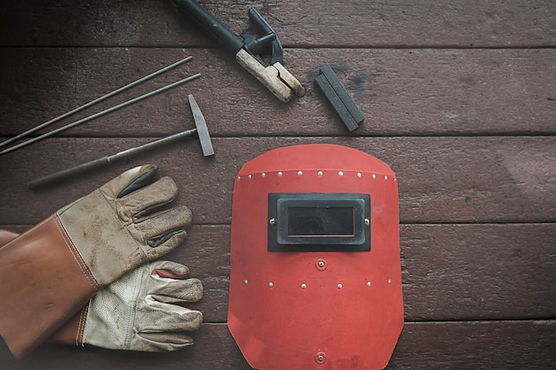 Ausrüstung auf hölzernem schreibtisch mit dem mann, der im werkstatthintergrund arbeitet.