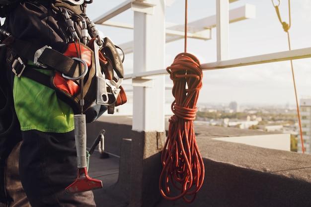 Ausrüstung des industriellen bergsteigers auf dem dach des gebäudes während der industriellen hochhausarbeiten. kletterausrüstung vor arbeitsbeginn. zugang für seilarbeiter. konzept der städtischen werke. platz kopieren