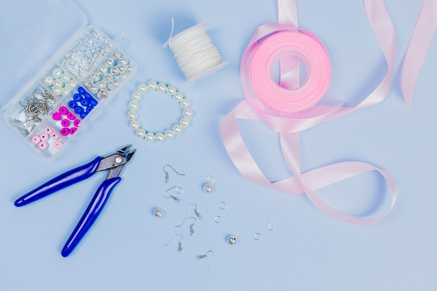 Ausrüstung für die herstellung der handgemachten ohrringe mit rosa band auf blauem hintergrund