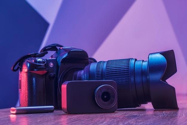 Ausrüstung für fotografie und videofilm. fotokamera mit objektiv, aktionskamera und usb-flash-laufwerk auf einem holztisch in einem studio mit kreativem licht.