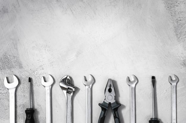 Ausrüstung für reparatur und bau auf einem grauen tischzangenschlüssel und schraubendreher