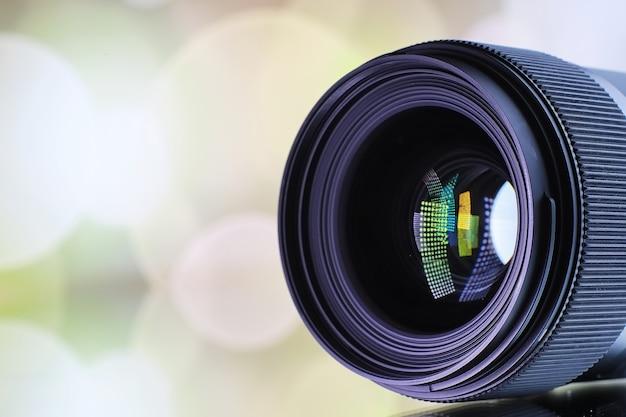 Ausrüstung videograf und fotograf. linsen auf dem tisch vor dem hintergrund heller lampen. blendung und bokeh in der spiegelung des kameraglases.