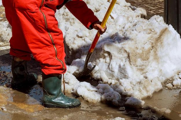 Ausrüstung von der arbeitskraft, die schnee von der straße im winter fegt