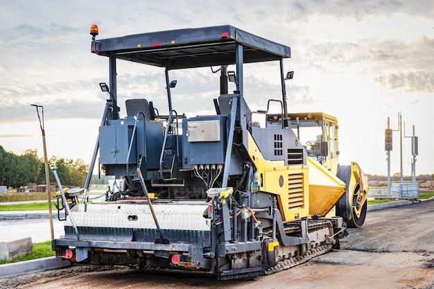 Ausrüstung zum asphaltieren. asphaltfertiger und schwere vibrationswalze. bau neuer straßen und straßenkreuzungen. schwere bauindustriemaschinen.