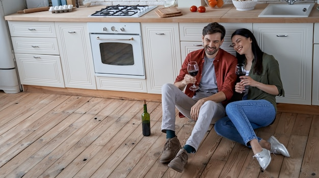 Ausruhen nach dem kochen der jungen glücklichen romantischen paarfrau und des ehemanns, die auf dem boden im sitzen
