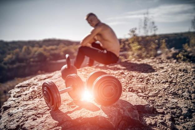 Ausruhen nach schwerem training in einem steinbruch. intensives training. starker attraktiver bodybuilder. lebensstil. felsige landschaft.